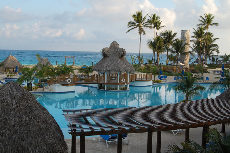 Piscină a unui hotel din Punta Cana, înconjurată de palmieri și construcții de lemn